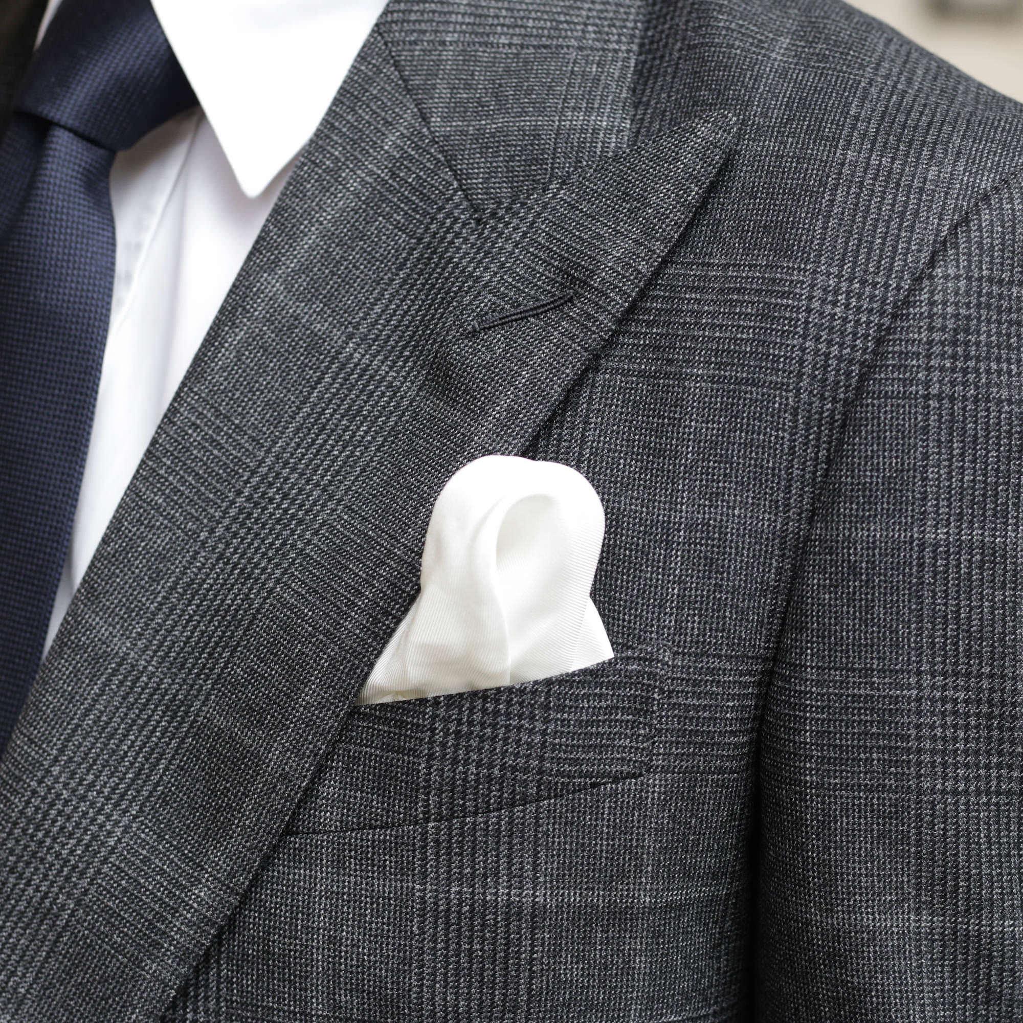 pochette de costume blanche sur tissu gris