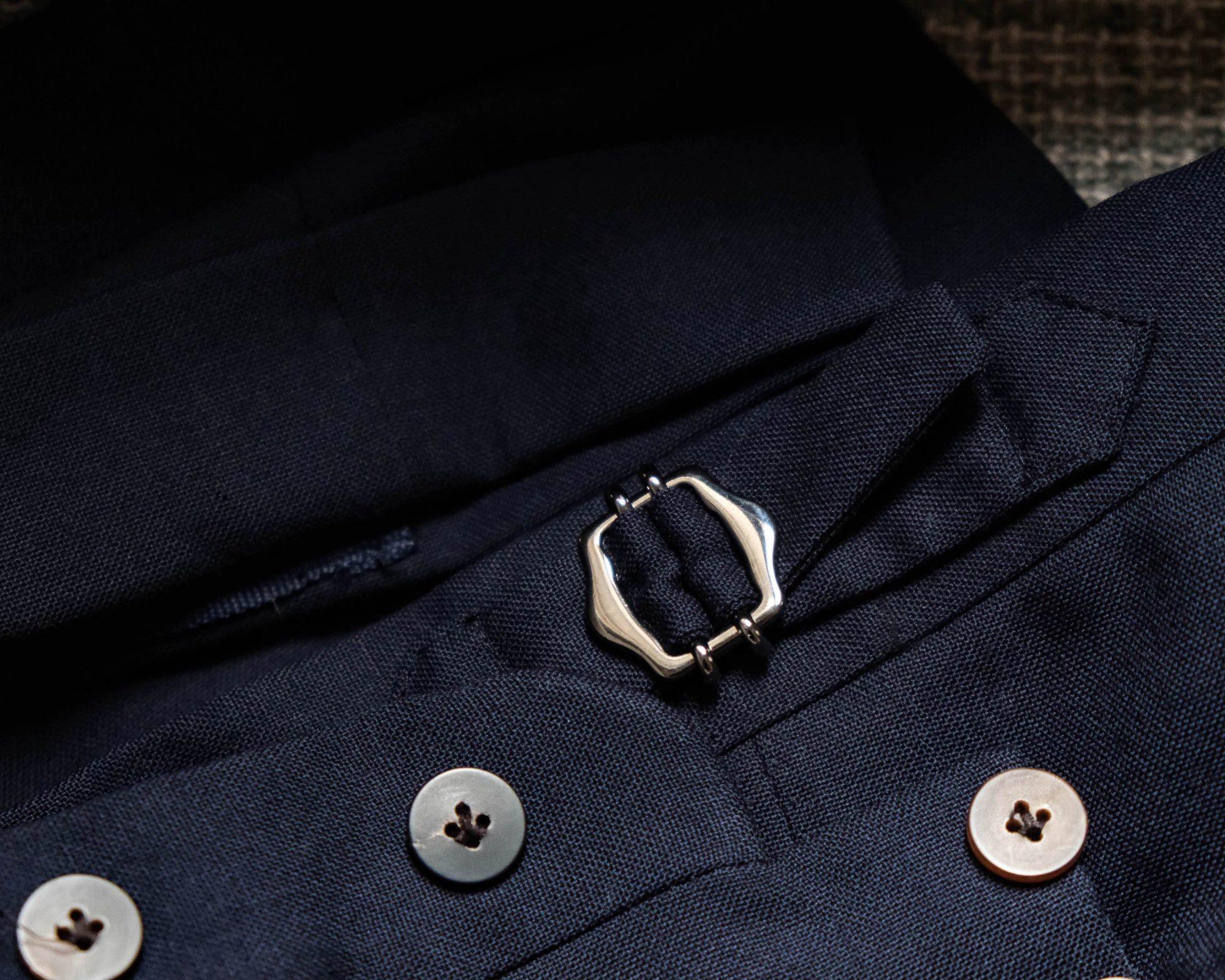 Patte de serrage côté du pantalon de costume.