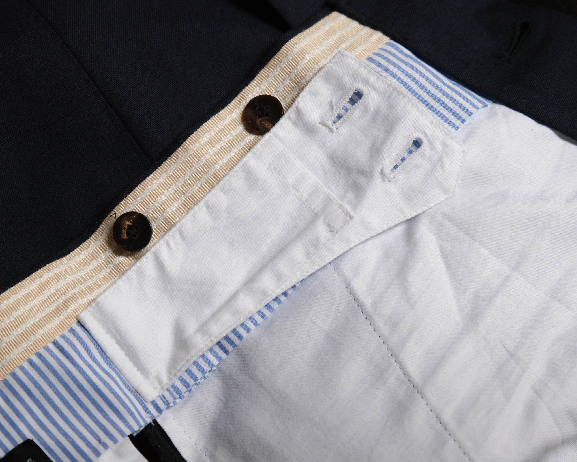 Patte boutonnée de maintien de la partie avant d'un pantalon de costume. Ici avec une poche cachée.